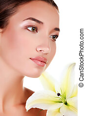 Face of a beautiful girl with a fresh flower lily