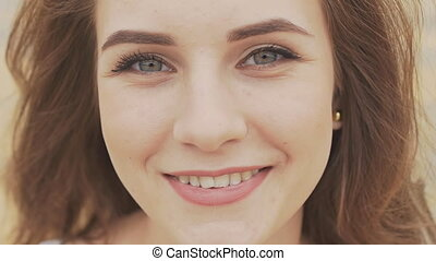 Face of a beautiful young girl with deep blue eyes close-up. On the face neat day makeup. Sensual look.