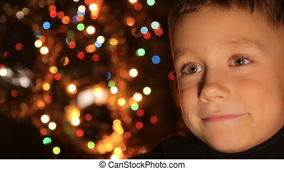 Face of a boy against the background of Christmas lights in...