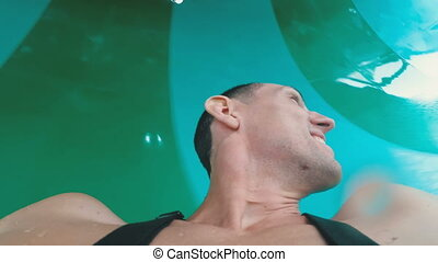 Face of a man descending from extreme water slides. First...