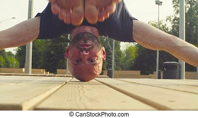 Face of a man doing headstand in the park