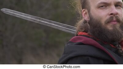 Face of a man with a beard with a sword on his shoulder close-up
