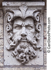 Face of a man with beard stone sculpture