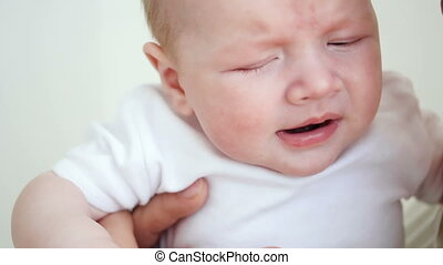 face of a newborn closeup at home sitting at his father