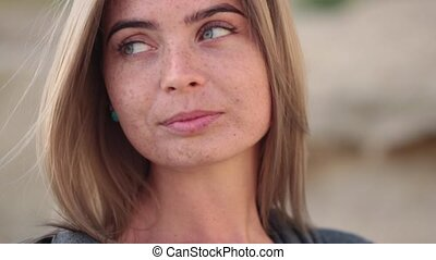 Face of a pretty shy girl with freckles, shot with the effect of a moving camera on a blurred background