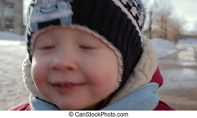 Face of a small boy with very expressive eyes in winter clothes.