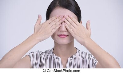 Face of beautiful Asian businesswoman covering eyes as three...