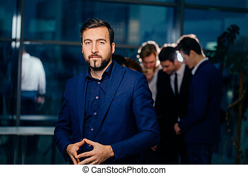 beautiful man on background of business people