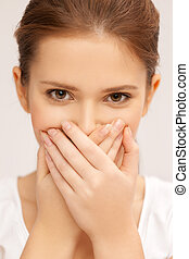 face of beautiful teenage girl covering her mouth - speak no...