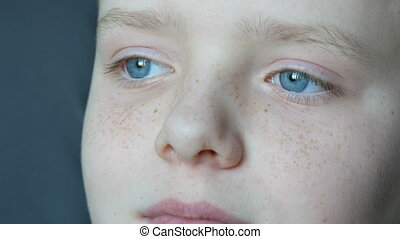 Face of beautiful teenager with freckles close-up view. A boy with blue eyes looking into the distance