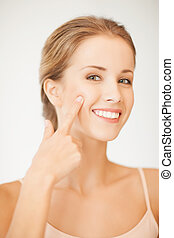 woman pointing at her cheek - face of beautiful woman ...