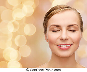 health and beauty concept - closeup of face of beautiful young woman with closed eyes