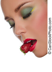 face of beautiful woman with strawberry in mouth