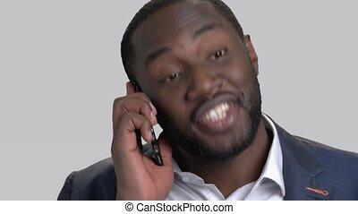 Face of black businessman talking on phone.