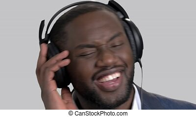 Face of black cheerful man in headphones.