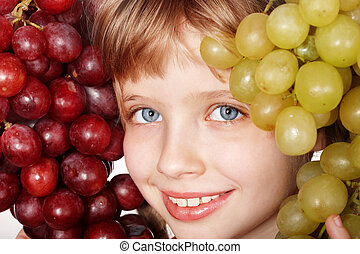 Face of child girl with grapes.