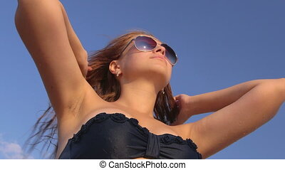 Face of cute girl in sunglasses on the beach against sky close-up