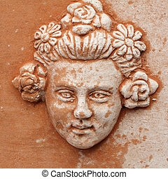 face of girl with elegant coiffure with flowers - decorative relief in tuscan terracotta