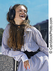 face of girl with head-phones - Happy girl is listening...