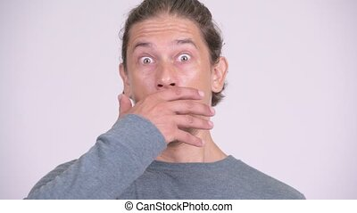 Face of handsome man covering mouth and looking surprised -...