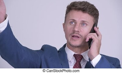 Face of happy bearded businessman talking on the phone