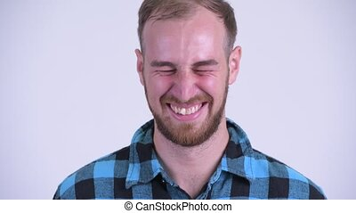 Face of happy bearded hipster man laughing