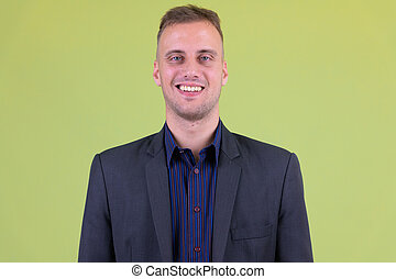 Face of happy handsome businessman in suit smiling