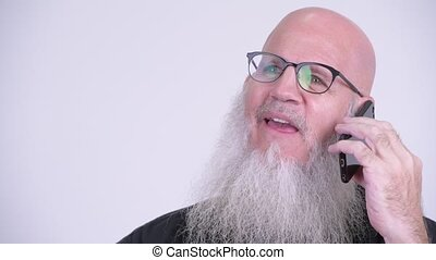Face of happy mature bald bearded man thinking while talking on the phone
