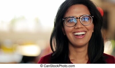 face of happy smiling young woman in glasses - people,...