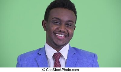 Face of happy young African businessman in suit smiling