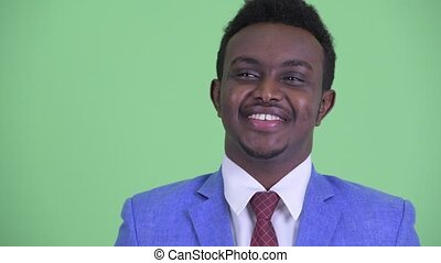 Face of happy young African businessman in suit thinking