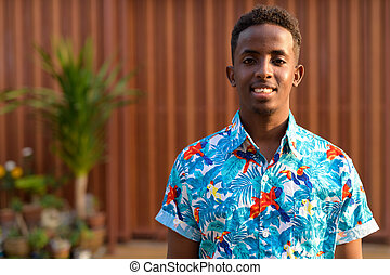 Face of happy young African tourist man with Afro hair smiling outdoors