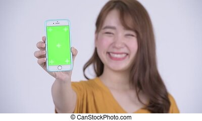Face of happy young Asian woman showing phone