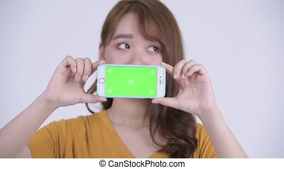 Face of happy young Asian woman thinking while showing phone