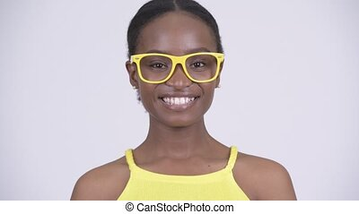 Face of happy young beautiful African woman smiling with yellow eyeglasses