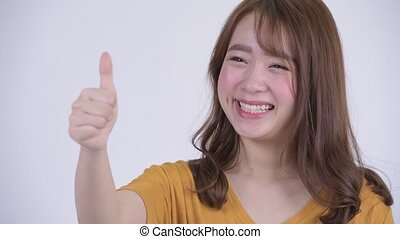 Face of happy young beautiful Asian woman giving thumbs up