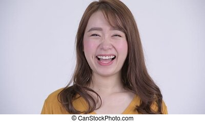 Face of happy young beautiful Asian woman looking surprised