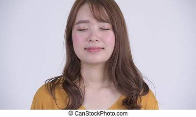 Face of happy young beautiful Asian woman relaxing with eyes closed