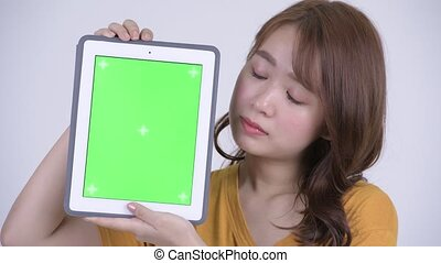 Face of happy young beautiful Asian woman showing digital tablet