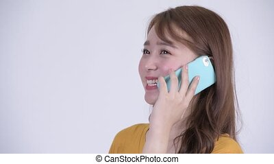 Face of happy young beautiful Asian woman talking on the phone