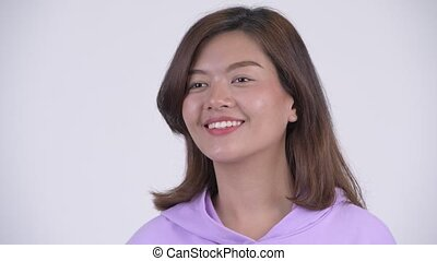 Face of happy young beautiful Asian woman thinking