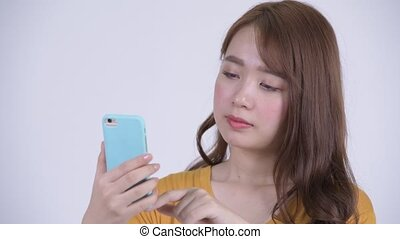 Face of happy young beautiful Asian woman using phone