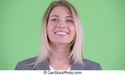 Face of happy young blonde businesswoman nodding head yes -...