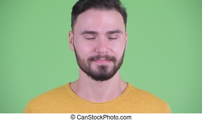 Face of happy young handsome bearded man nodding head yes -...