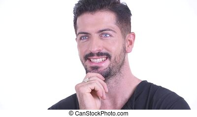 Face of happy young handsome bearded man thinking and looking up