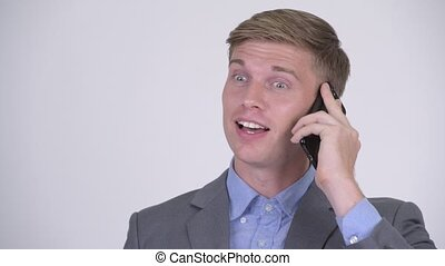 Face of happy young handsome businessman talking on the phone