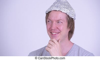 Face of happy young man with tinfoil hat thinking and looking up