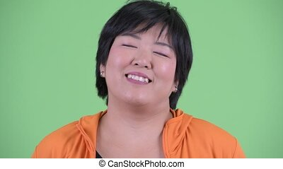 Face of happy young overweight Asian woman relaxing with...