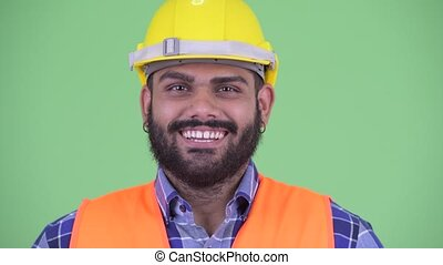 Face of happy young overweight bearded Indian man...