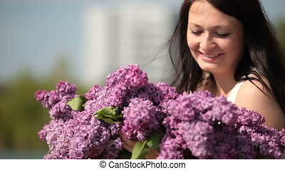Face of happy young woman with a bouquet of lilacs in the spring close up